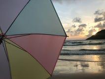 Sonnenuntergang auf Strand mit buntem Pastellregenschirm und schönem Sonnenlicht lizenzfreies stockfoto