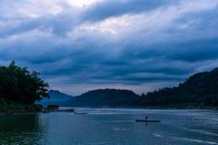 Sonnenuntergang beim Mekong Blaue Stunde mit vielen Wolken Einige Boote im Fluss Bewölkte Szene in Luang Prabang, Laos lizenzfreie stockfotografie