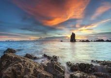 Sonnenuntergang bewegt Wimpernansatzauswirkungsfelsen auf dem Strand wellenartig Lizenzfreie Stockfotografie
