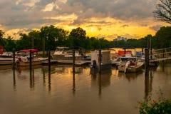 Sonnenuntergang in dem Fluss mit Booten und Docks lizenzfreies stockbild