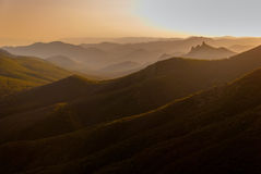 Sonnenuntergang in den bewaldeten Bergen Stockfotos