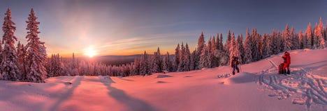Sonnenuntergang in den schneebedeckten Bergen, mit zwei Skifahrern und Touristen auf der Steigung Stockfoto