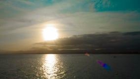 Sonnenuntergang in den Wolken und in den Bergen auf dem Meer in der Touristensaison mit Booten und Fallschirm stock footage