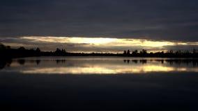 Sonnenuntergang, der über einen See nachdenkt Stockbild