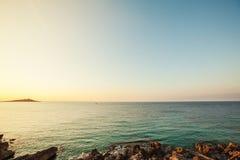 Sonnenuntergang an der Küste, Bank des Flusses Ufer mit Steinen stockfotografie