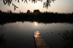 Sonnenuntergang an der Küste des Sees und der kleinen Brücke Stockfotos