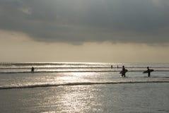 Sonnenuntergang, der am kuta Strand surft. Stockfoto