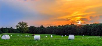 Sonnenuntergang in der Wiese mit Hay Bales Lizenzfreie Stockbilder