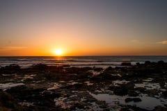 Sonnenuntergang des felsigen Strandes Stockfotografie