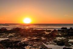 Sonnenuntergang des felsigen Strandes Lizenzfreie Stockbilder