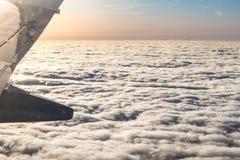Sonnenuntergang durch das Flugzeugfenster über den Wolken lizenzfreies stockbild