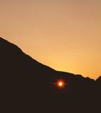 Sonnenuntergang durch das Herz formte Loch in der Klippe Stockbild