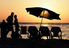 Sonnenuntergang durch das Meer mit Schattenbildern Lizenzfreie Stockfotos