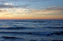 Sonnenuntergang durch das Meer, Rotglühen Lizenzfreies Stockbild