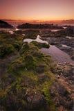 Sonnenuntergang durch den Ozean Stockfotos