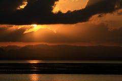 Sonnenuntergang durch den Strand Lizenzfreies Stockfoto