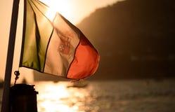Sonnenuntergang durch italienische Marineflagge auf Segelboot vor der Küste von C lizenzfreies stockbild