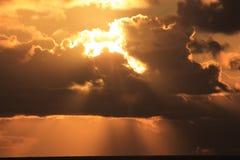 Sonnenuntergang durch Wolken Lizenzfreie Stockfotos