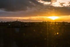 Sonnenuntergang durch Zug-Fenster-Beifahrersitz-Ackerland draußen Stockbild