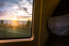 Sonnenuntergang durch Zug-Fenster-Beifahrersitz-Ackerland draußen Stockfoto