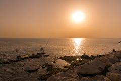 Sonnenuntergang entlang der Küste vom Libanon mit Schattenbild von Mannfischerei lizenzfreie stockfotografie