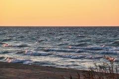 Sonnenuntergang entlang schönem Michiganseestrand mit Ansicht von Chicago-Skylinen im weiten Hintergrund lizenzfreie stockfotos