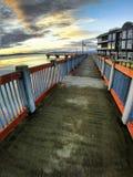 Sonnenuntergang fängt über Ufergegenddock nahe bei ikonenhaftem Hotel an lizenzfreies stockbild