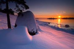 Sonnenuntergang färbte schneebedeckte Steine stockfoto