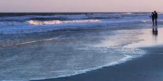 Sonnenuntergang-Fischen auf dem Ufer lizenzfreie stockbilder