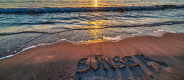 Sonnenuntergang geschrieben in den Sand lizenzfreie stockfotografie