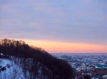 Sonnenuntergang heute in der Großstadt, Kiew, Ukraine Stadt unter Schnee, Sonnenuntergangzeit Stockfotografie