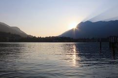 Sonnenuntergang hinter Bergen mit See in einem Frühherbst Stockbild