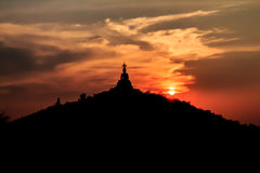 Sonnenuntergang hinter dem Buddha auf Berg, Ratchaburi Thailand Prozessfarbe Stockfotografie
