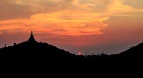 Sonnenuntergang hinter dem Buddha auf Berg, Ratchaburi Thailand Prozessfarbe Lizenzfreie Stockfotografie