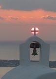 Sonnenuntergang hinter dem Kreuz auf einem Kirchenglocketurm Stockbilder