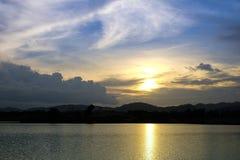 Sonnenuntergang hinter dem See und dem Hügel bei Einbruch der Dunkelheit Lizenzfreies Stockfoto