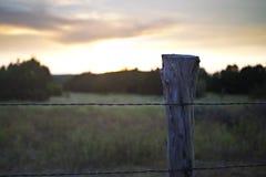 Sonnenuntergang hinter Drahtzaun und -Beitrag Stockfoto
