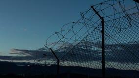 Sonnenuntergang hinter einem Stacheldraht im Gefängnis stock video footage