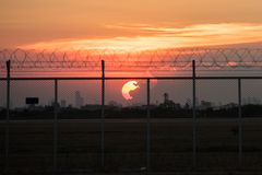 Sonnenuntergang hinter undeutlichem Zaun Stockfotos
