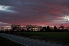 Sonnenuntergang hinunter eine Landstraße Stockbilder