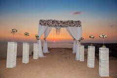 Sonnenuntergang Hochzeitszeremoniebogen mit Blumen dekorativen arrangemen Lizenzfreies Stockfoto