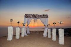 Sonnenuntergang Hochzeitszeremoniebogen mit Blumen dekorativen arrangemen Stockbilder