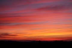 Sonnenuntergang im bunten roten Himmel mit Landschaftsschattenbild Stockbild