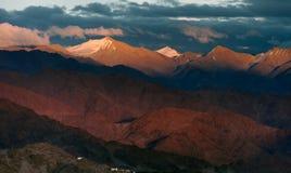 Sonnenuntergang im Gebirgstal: die hohen Hügel sind teils sonnenbeschienes und gemaltes Rosa, teils im Schatten, deren Eindruck e Lizenzfreie Stockbilder
