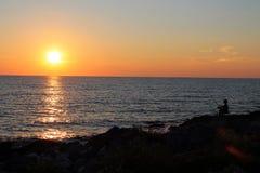 Sonnenuntergang im Meer mit Fischer Lizenzfreie Stockfotografie