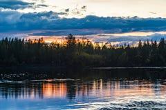 Sonnenuntergang im Waldwald durch den Fluss Russland lizenzfreie stockbilder