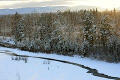 Sonnenuntergang im Winterwald der Fluss fließt unter das Eis Stockbilder