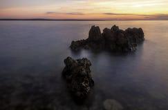 Sonnenuntergang-Küstenlinie mit Felsen lizenzfreie stockfotos