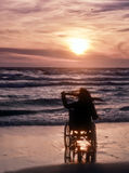 Sonnenuntergang, macht Besichtigung auf dem Strand eine Frau auf Rollstuhl Lizenzfreie Stockbilder