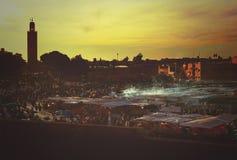 Sonnenuntergang in Marrakesch an Jeema EL Fna mit Lebensmittelständen, -rauche, -Skylinen und -minarett Lizenzfreie Stockfotos